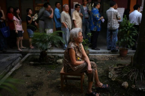 A woman sits as voters queue to cast their votes during the 13th General Election on 5 May 2013.