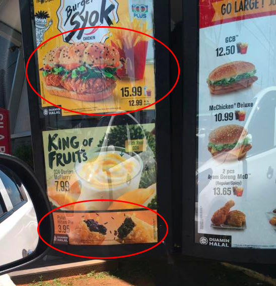 Burger Syok Ayam and Pulut Hitam Pie (circled in red, top and bottom respectively) as displayed on the menu board of a drive-thru in Tawau, Sabah.
