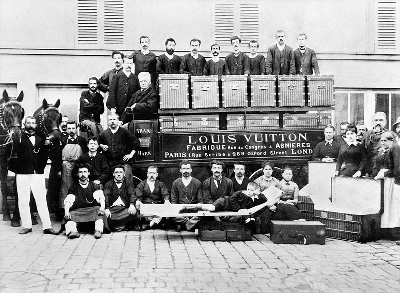 In the courtyard of the Asnières workshops, around 1888, Louis, Georges, and Gaston L. Vuitton (sitting on a bed trunk).