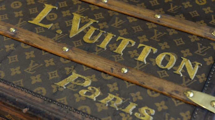 A vintage Louis Vuitton trunk with the Monogram Canvas pattern.