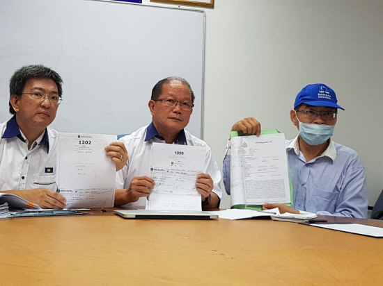 Lim (in face mask) with two MCA officials.