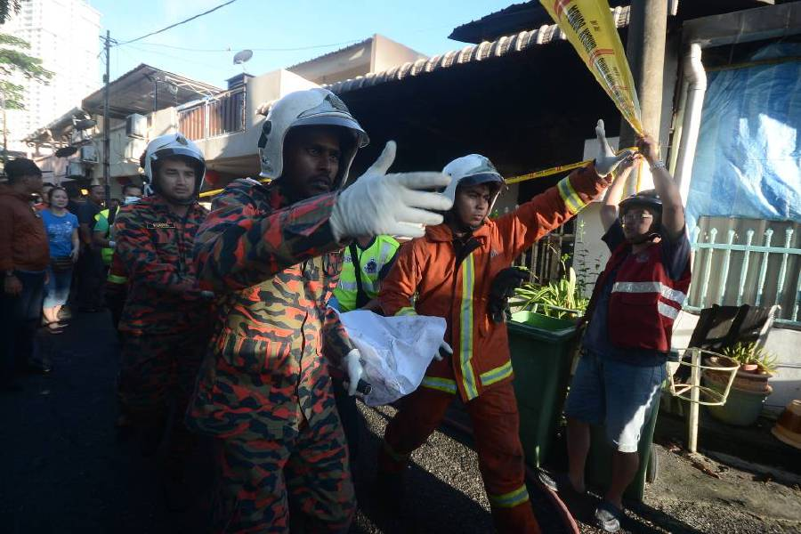 Firemen carrying the body of one of the four victims.