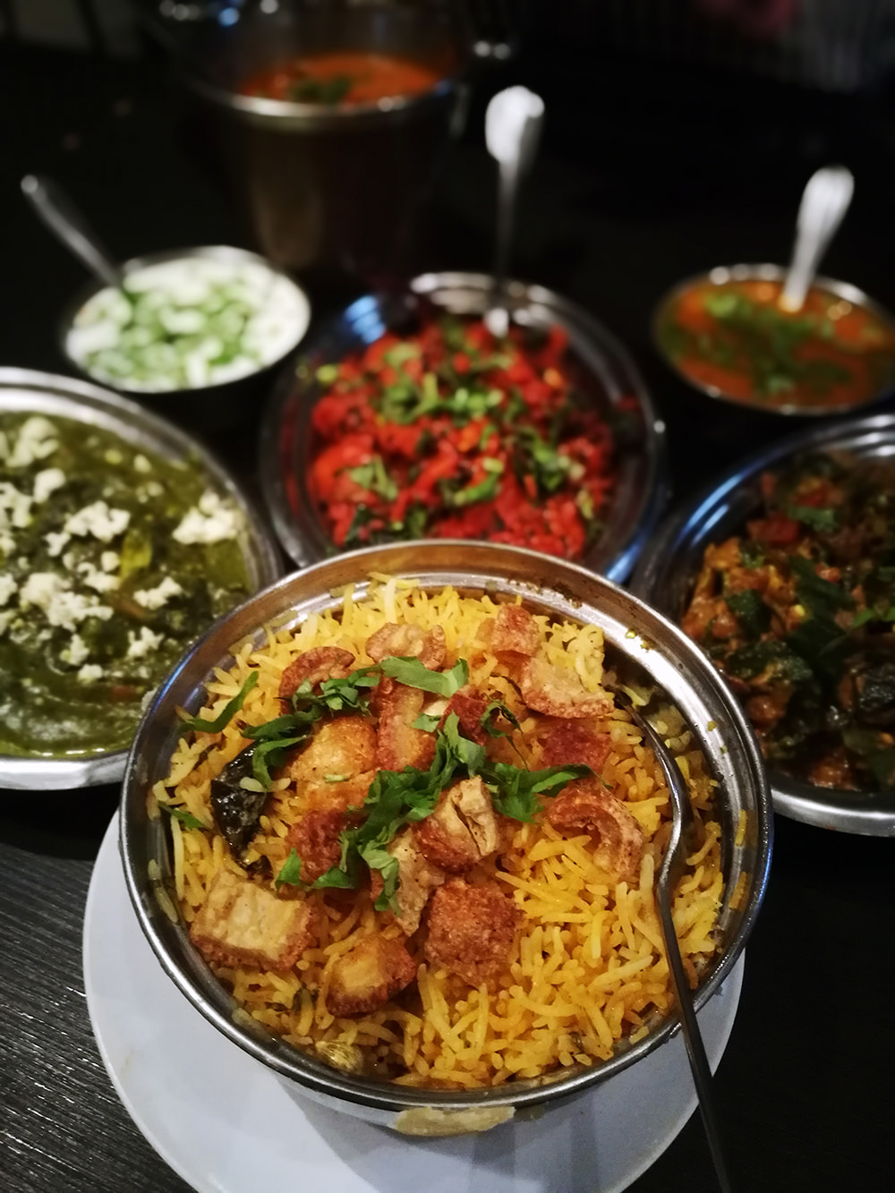 Clockwise, from middle: Siew Yoke Biryani, Palak Paneer, Pork 65 Masala, and Bindhi Masala.