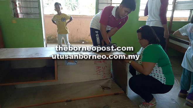Parents helping to repair a broken cabinet in one of the school hostels.