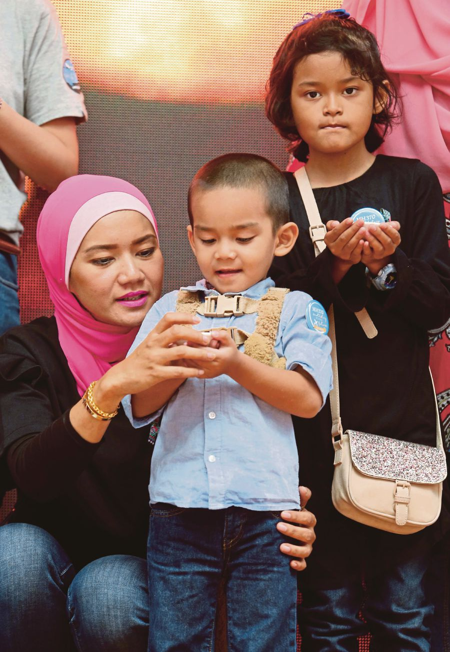 Intern Maizura Othman (left) together with her children Iman Mohd Hazrin (right) and Muhammad Hazrin (middle) at The Square, Publika.