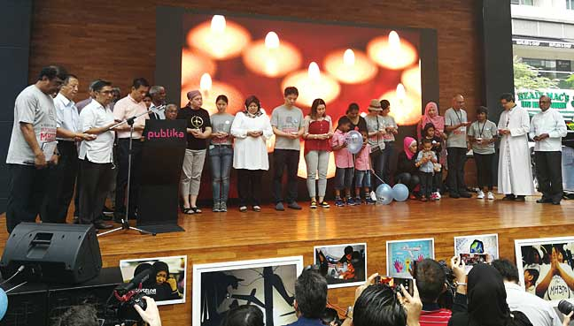 Some families of the MH370 victims on stage during a multi-faith prayer session at the remembrance event at Publika.