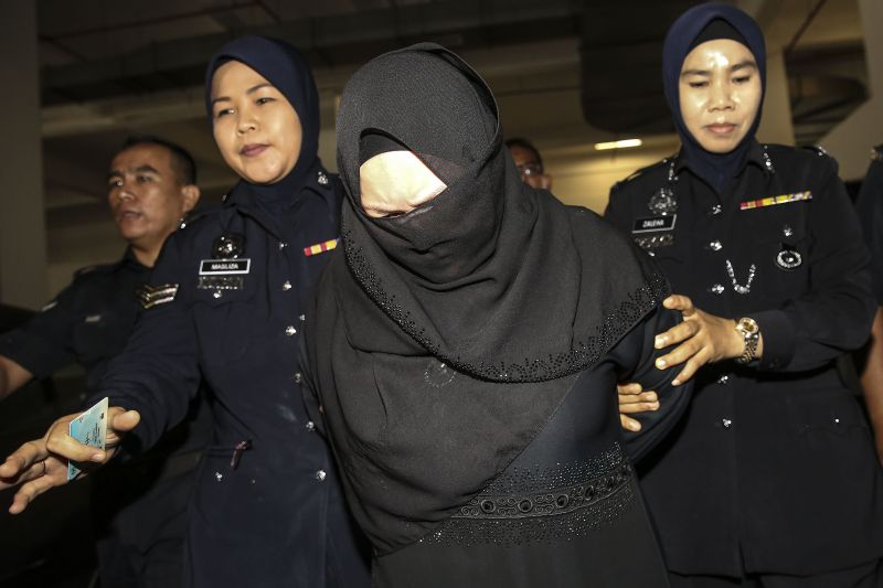 Datin Rozita is seen being escorted by police at the Shah Alam High Court today.