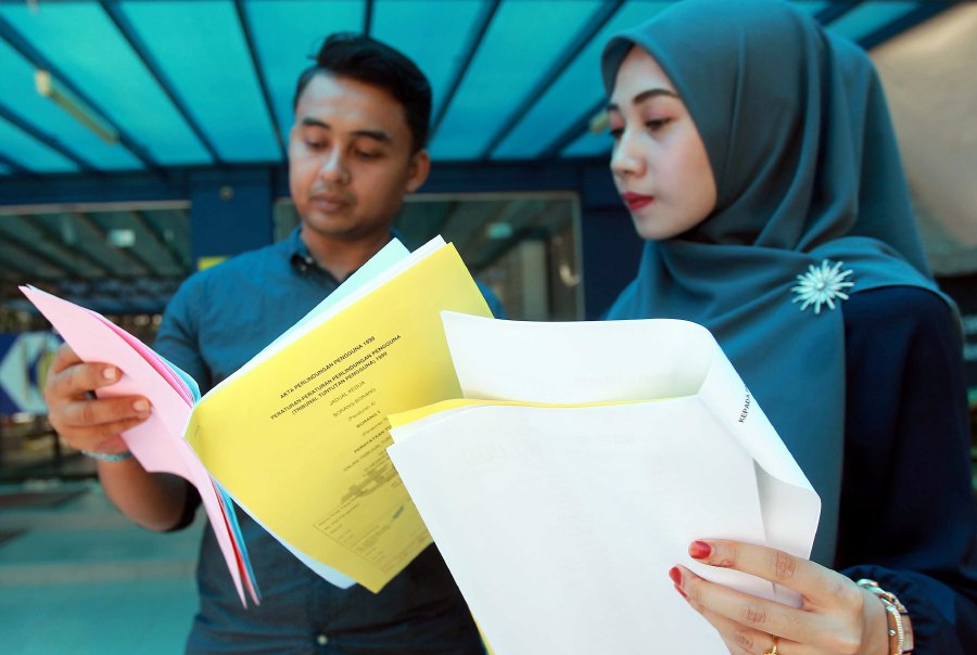 The newlyweds, Mohd Nor Afzarizal Zulkipli and Amy Nor Alice Kamaruddin, with a copy of the report, lodged against the caterer at the Kuantan's KPDNKK.