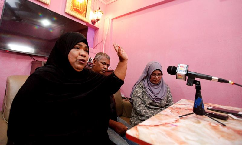 Hawa Jaafar, sister to Adam Jaafar, speaks to the media at her home.