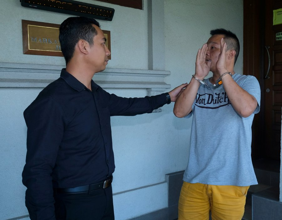 Lai tries to cover his face from being photographed as he leaves the KL Magistrate's Court.