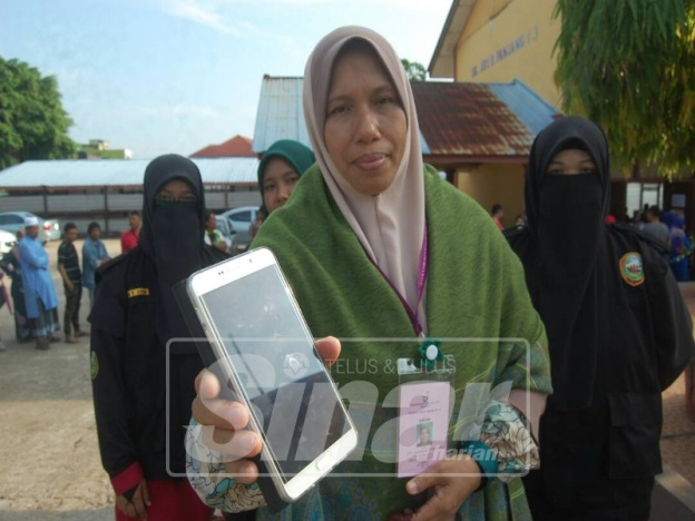 PAS candidate Siti Zailah Mohd Yusoff showing reporters a photo that depicts ballot papers for Parliament and DUN were put into the same box.