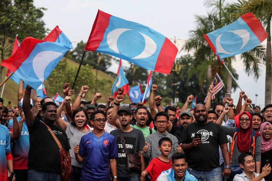 Supporters of former Malaysian Prime Minister Tun Dr Mahathir Mohamad shout slogans and wave flags in front of the Istana Negara in Kuala Lumpur on 10 May.