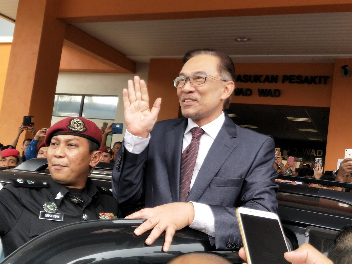 Anwar waving at the crowd of reporters and journalists outside of the hospital.