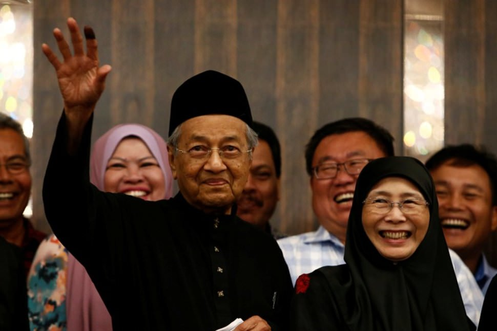 PM Tun Dr Mahathir gestures beside his Deputy PM Dr Wan Azizah, after being sworn in.