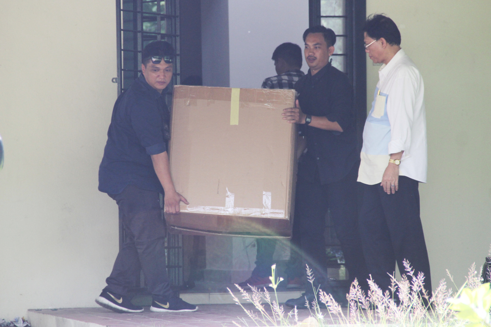 Police officers were seen carting away boxes from the house in Precinct 10, Putrajaya.