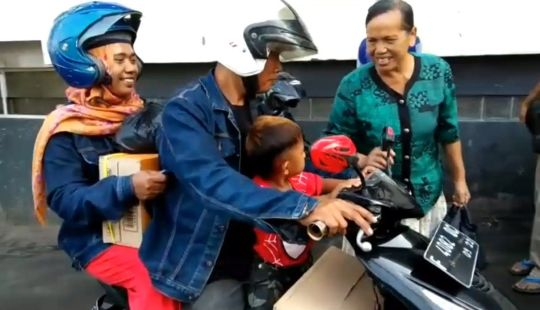 Two-year-old Rap sitting on a motorbike with his parents.