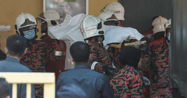 Firemen carrying a victim's body out of a tahfiz school after a fire last year.