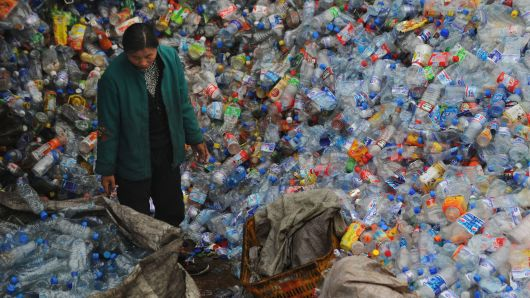 A woman stands amid a huge pile of used plastic bottles at a plastics recycling mill in Wuhan, China.