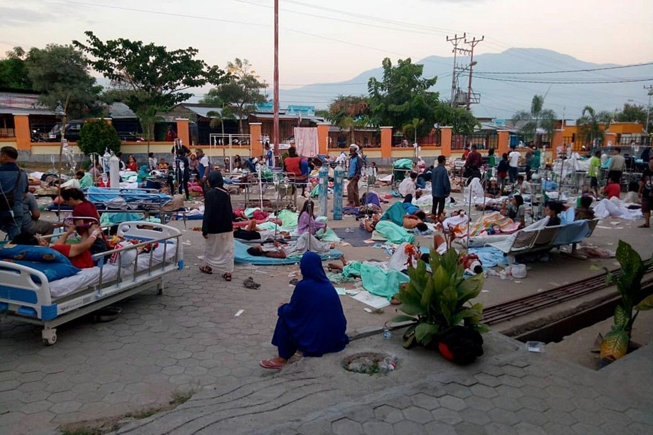 Victims receive treatments in front of a hospital in Palu, Central Sulawesi.