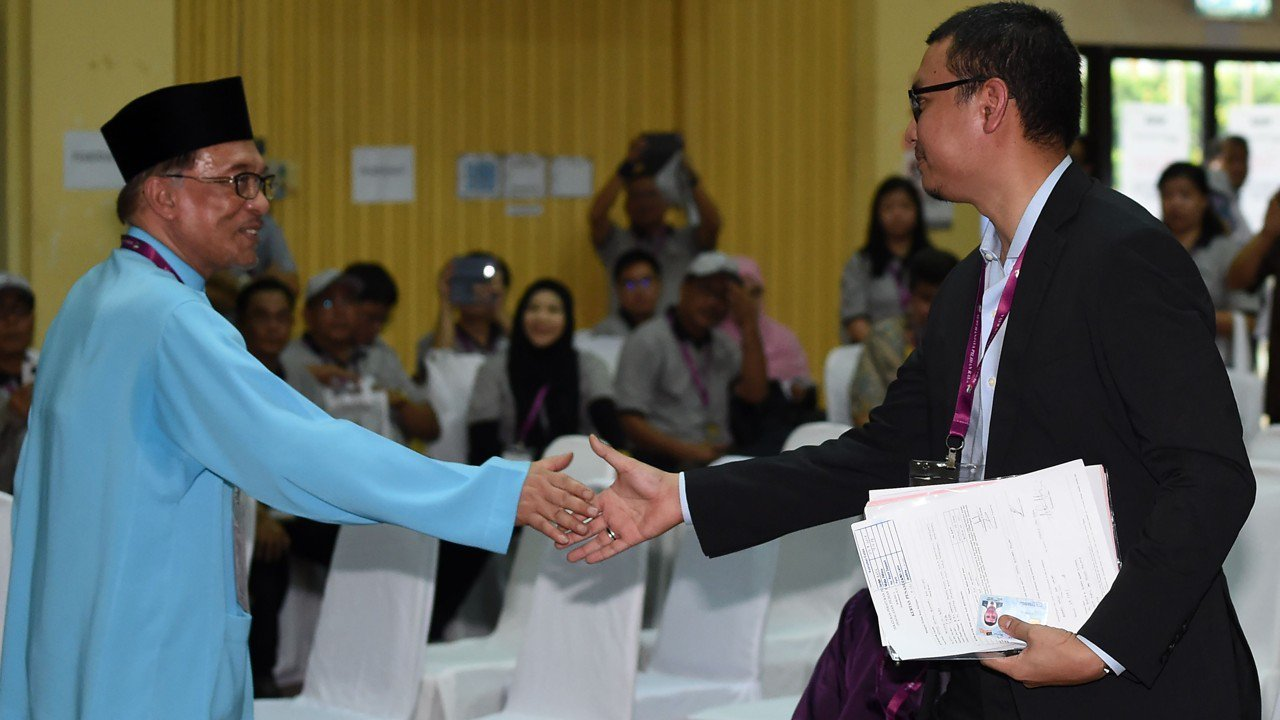Anwar shakes hands with Saiful after submitting his documents at the Port Dickson nomination centre on 29 September.