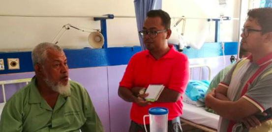 Abdul Manan (left) recounting his son's death due to food poisoning.