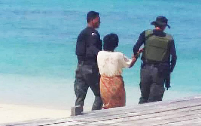 Sabah woman being escorted after slashing her children's throats.