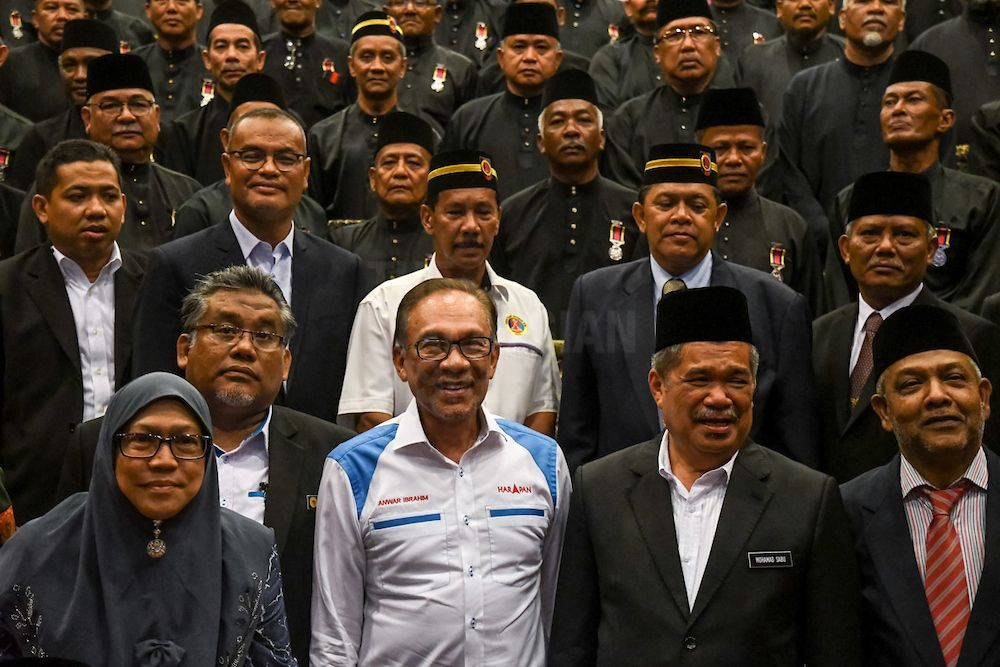 Newly-elected Port Dickson MP Anwar Ibrahim (in white) with Defence Minister Mohammad Sabu on his left at the said army veterans' dinner.