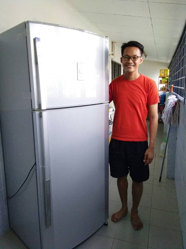 red chinese man with spectacles standing next to a silver hitachi refrigerator