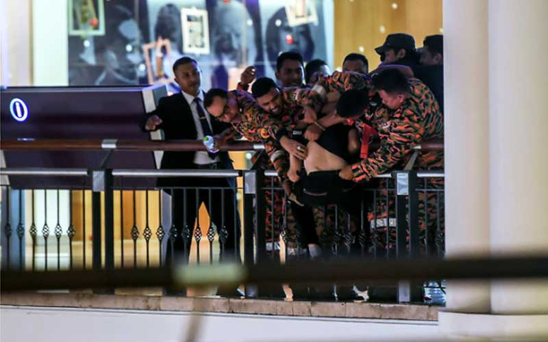 This Bernama photo shows Fire brigade personnel grabbing the man after spending more than two hours to try and talk him out of committing suicide.
