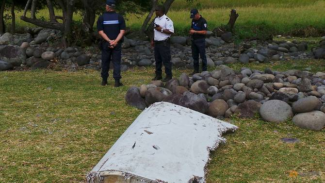 French gendarmes and police stand near a large piece of plane debris which was found on the beach in Saint-Andre, on the French Indian Ocean island of La Reunion. Taken 29 July, 2015.