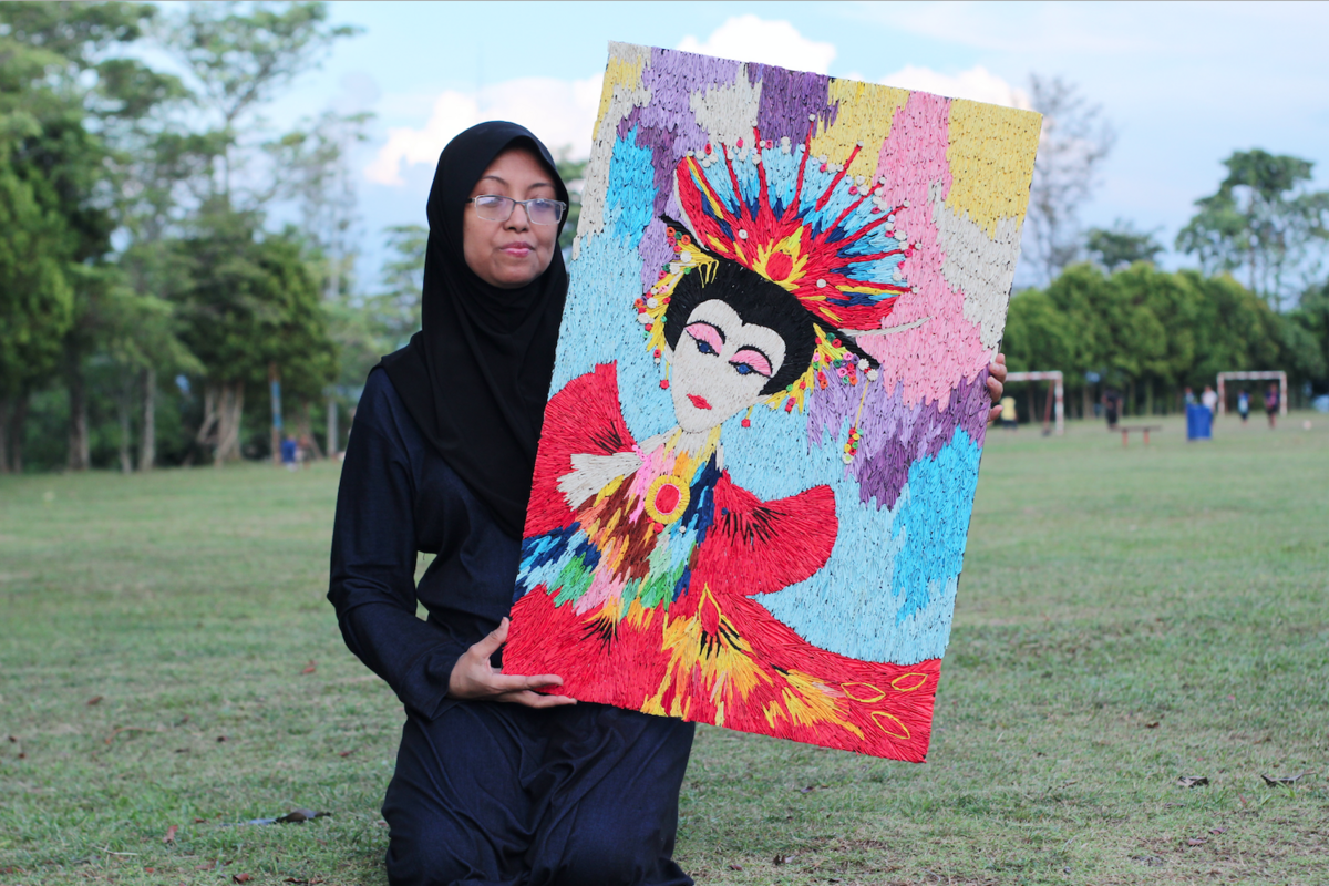Laily holding up one of her artworks.