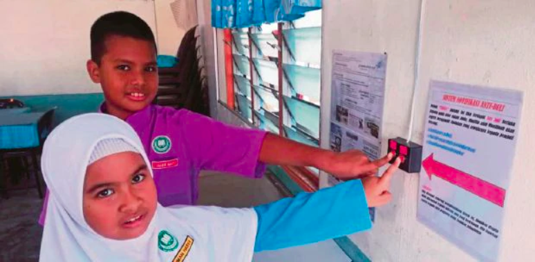 Umar with his little sister Hasya, showing the system he developed with his friends.