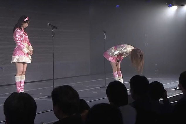 Yamaguchi bowing on stage as she apologises.
