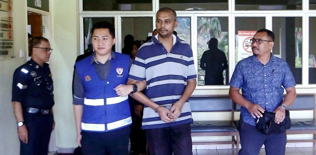 A. Mohanraj being escorted out by authorities at the Selayang Sessions Court.