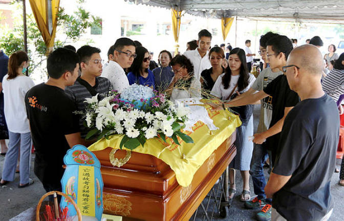 Family and friends of accident victim Moey Yun Peng paying their last respects at the Berapit Chinese cemetery in Penang.