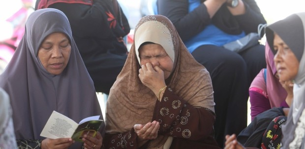 Abdul Bari's mother Masitah Awang (middle) unable to contain her tears during the special prayers session held for her son.