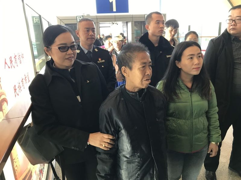 Kaewmanee Arjor (centre, in black) and her daughter Suchada Arjor (in green), together with Chiang Rai immigration officials.