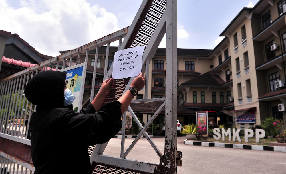 A notice being put up in front of SMK Pasir Putih to announce the temporary closure of the school due to toxic fumes from chemicals dumped into the nearby Sungai Kim Kim, March 7.