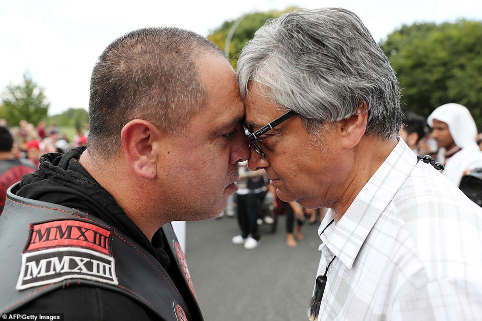 Waikato Muslim Association president Dr Asad Mohsi (right) touches noses in a traditional 'Hongi' greeting with a gang member (left).
