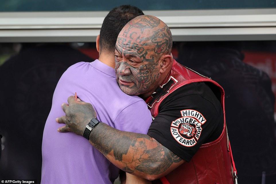 A member of the Mongrel Mob hugging a Muslim man.