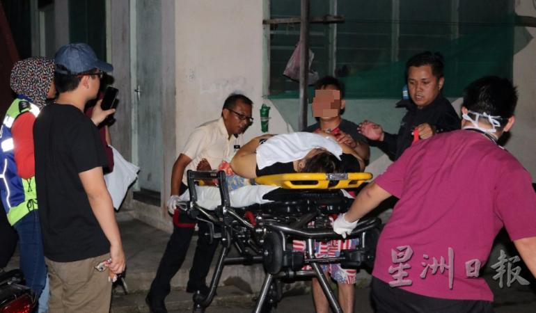 The victim being accompanied by the 28-year-old man (third from right) to the ambulance.