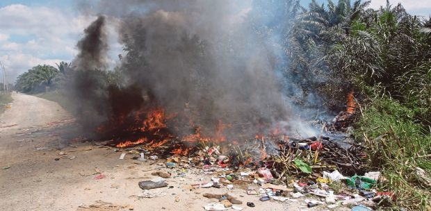 Illegal burning of plastic waste by the roadside in Jenjarom.