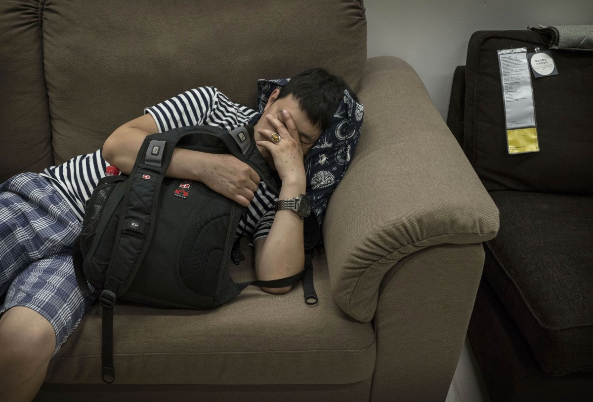 chinese man sleeping on brown ikea couch