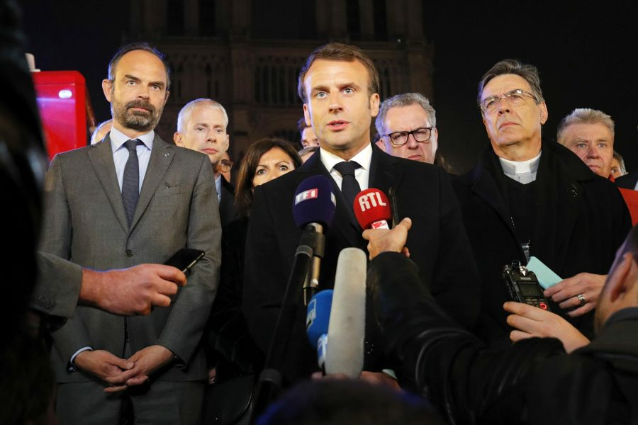 Archbishop of Paris Michel Aupetit, right, accompanies President Emmanuel Macron and other officials as he speaks outside Notre Dame Cathedral.