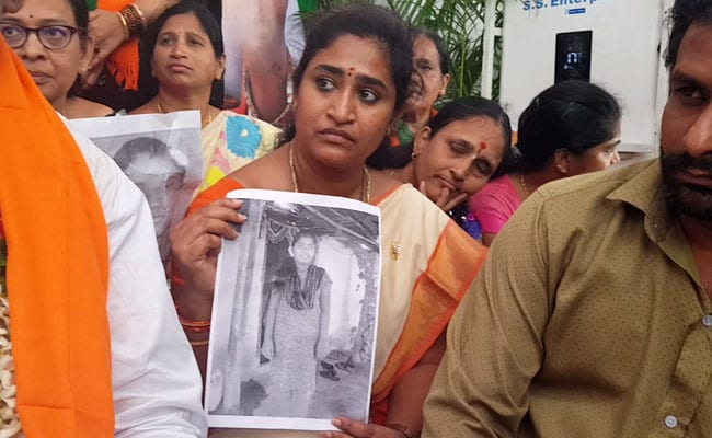 Activists holding photos of students who committed suicide over faulty exam results.