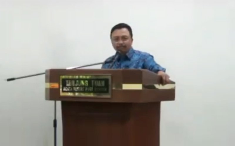 Abibullah, clad in a blue batik shirt, standing behind a podium, warning staff against voting for PH.
