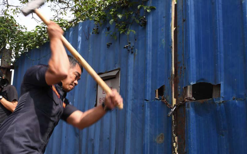 A Klang Municipal Council enforcement officer tries to smash open a lock at an illegal plastic recycling factory in Telok Gong during an operation in January.