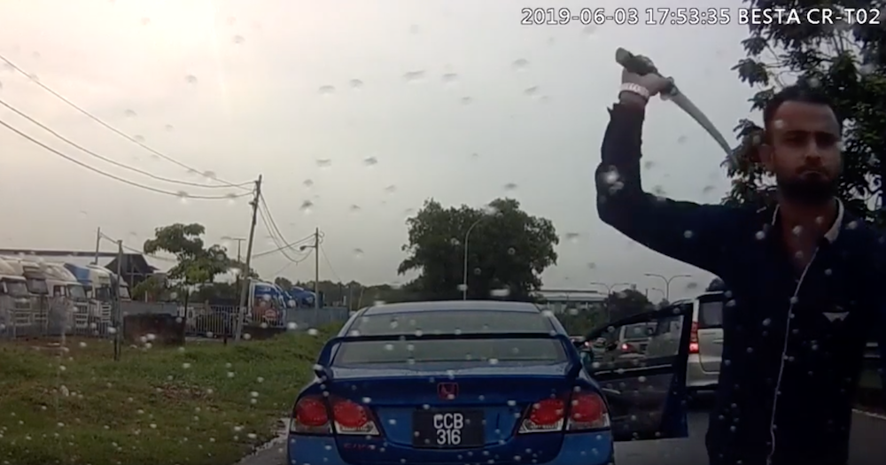 Screengrab showing the main suspect attacking a car with a parang on Monday.