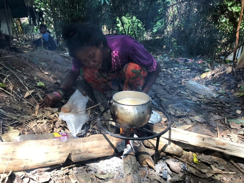 A woman cooking rice with water from Sungai Pertang, a stream located near Kuala Koh.