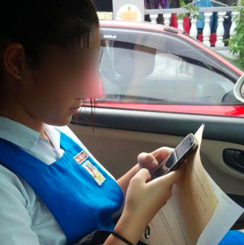 The student holding copies of the police report in her mother's car.